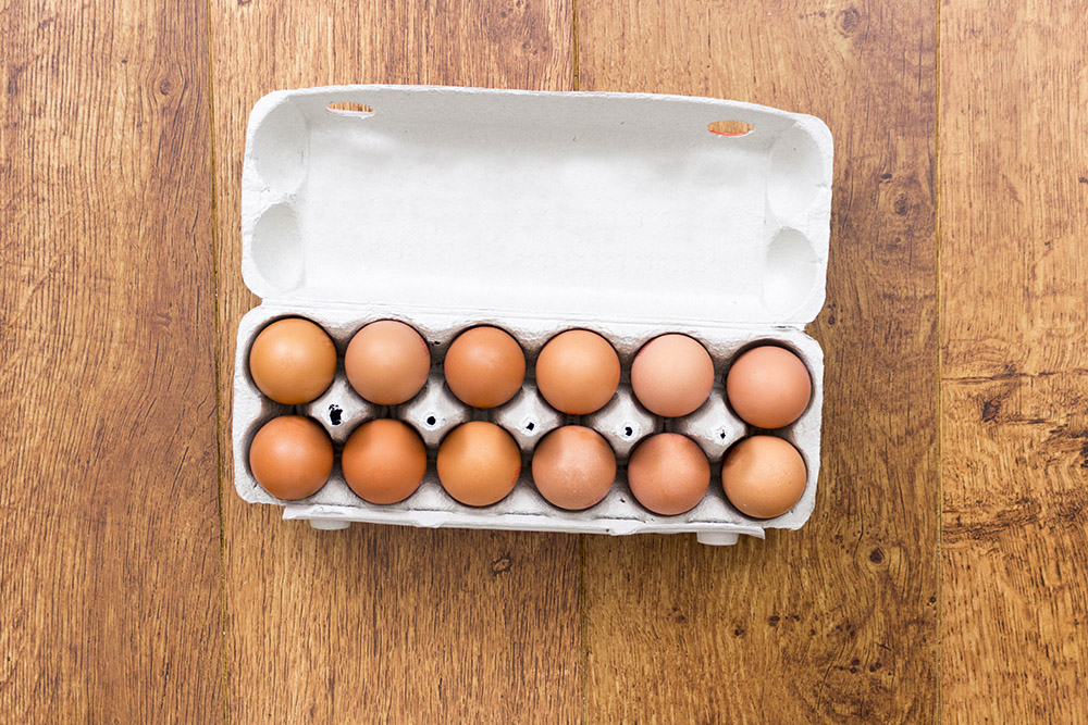 a dozen brown eggs in a cardboard box