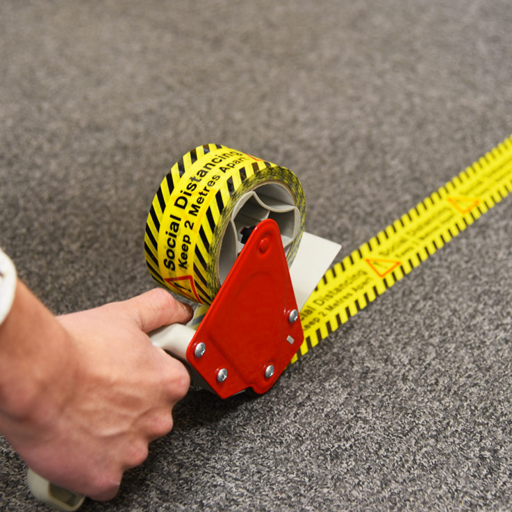 Social Distancing Printed Floor Marking Tape being applied to carpet